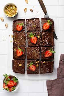 피스타치오 너트와 딸기는 가벼운 표면, 평면도, 수평 구성에 흰 종이에 초콜릿 사각형. 평평한 음식.