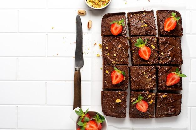 흰 종이에 피스타치오 견과류와 딸기를 넣은 초콜릿 사각형