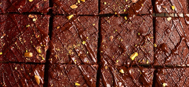 Chocolate squares with pistachio nuts and strawberries on a metal stand on a light stone background, top view, horizontal composition. flat lay