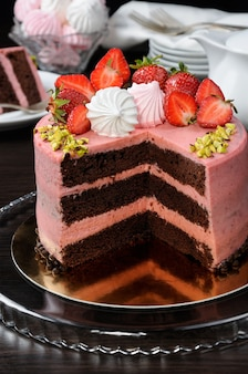 Chocolate strawberry cake decorated with berries, meringue and pistachios in a cut