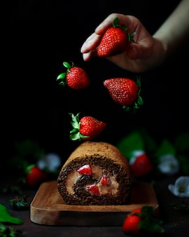 Chocolate strawberry sweet roll with levitating strawberries and woman hands,dark food photography