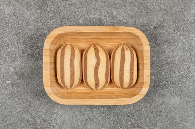 Шоколадное полосатое печенье на деревянной тарелке