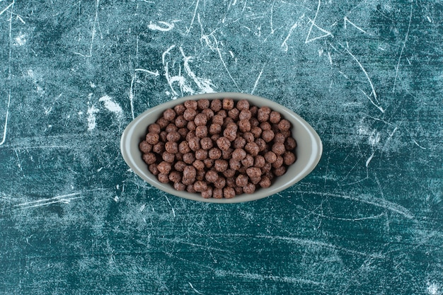 青い背景に、ボウルにチョコレートスイートコーンボール。高品質の写真