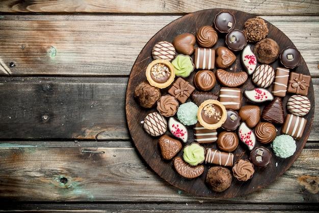 木の板にチョコレートのお菓子。木製の背景に。