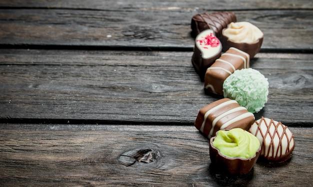 ナッツと様々なフィリングが入ったチョコレートスイーツ。木製の背景に。