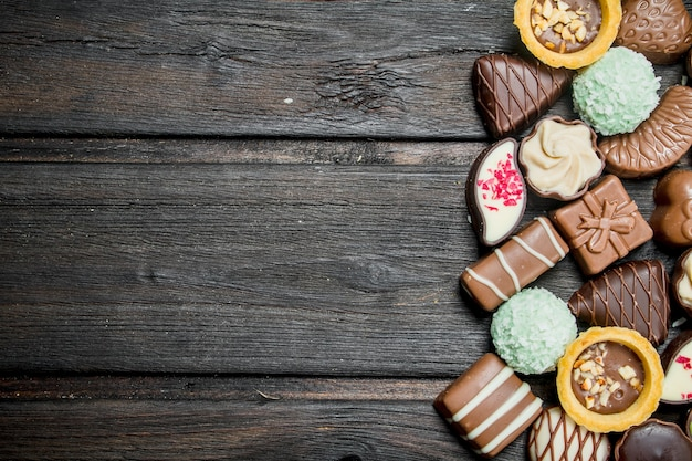 木製のテーブルにナッツとさまざまな詰め物が入ったチョコレート菓子。