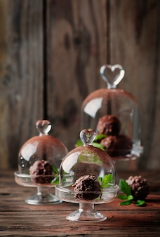 Chocolate sweets with nuts, mint and cacao on the vintage table