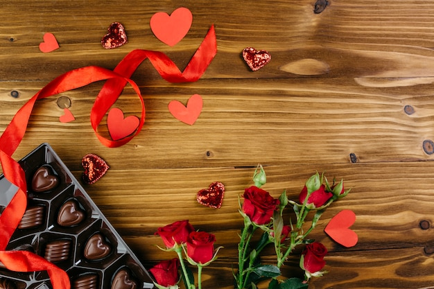 Chocolate sweets with roses on table