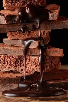 Шоколадный сироп капает на стек темный шоколад