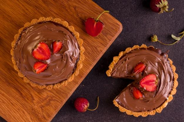 검은 배경에 딸기와 초콜릿 타르트입니다.