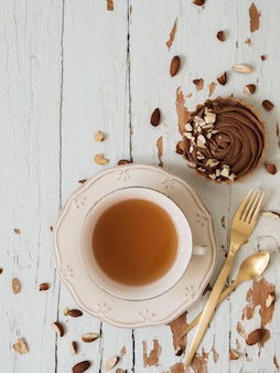 Chocolate tarts served almond nuts with cup of tea and golden cutlery on shabby white wooden background