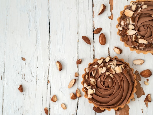 Chocolate tarts served with almond nuts on shabby white wooden surface