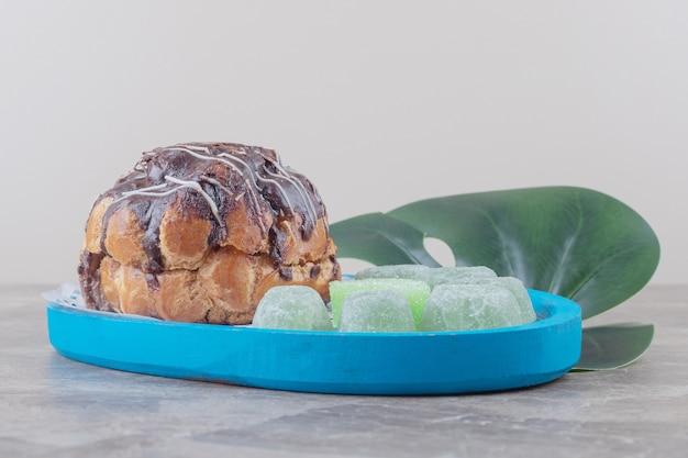 大理石の装飾的な葉の大皿にチョコレートをトッピングしたケーキとマーマレード