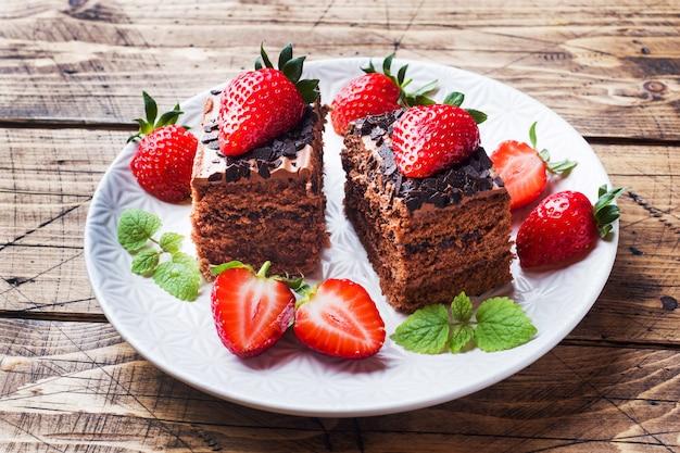 イチゴとミントのチョコレートトリュフケーキ。木製のテーブル。