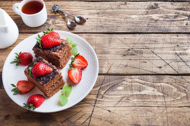 Chocolate truffle cake with strawberries and mint. wooden table. copy space