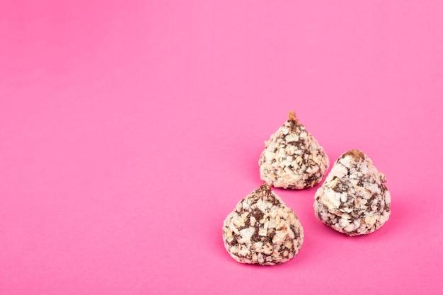 Шоколадные трюфельные конфеты с орехами на розовом фоне копируют пространство.