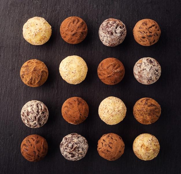 チョコレートトリュフ、ココアパウダー入りチョコレートキャンディー、チョコレートキャンディーコレクション。デザートプレートにココアパウダー、ココナッツ、刻んだヘーゼルナッツを詰めたチョコレートトリュフ。