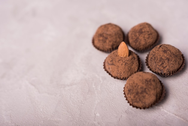 Chocolate truffle with almond on white concrete textured backdrop