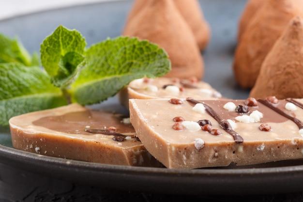 Chocolate truffle with piece of milk chocolate on blue ceramic plate on gray