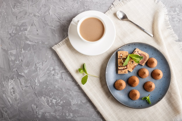 Chocolate truffle with piece of milk chocolate on blue ceramic plate.