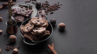Chocolate truffles and healthy oats cookies in utensil on black backdrop