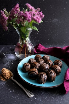 Chocolate truffles on blue plate flowers in vase on a dark background