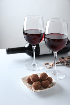 Chocolate truffles and glasses with red wine on white table