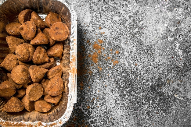 Шоколадные трюфели в миске на деревенском фоне