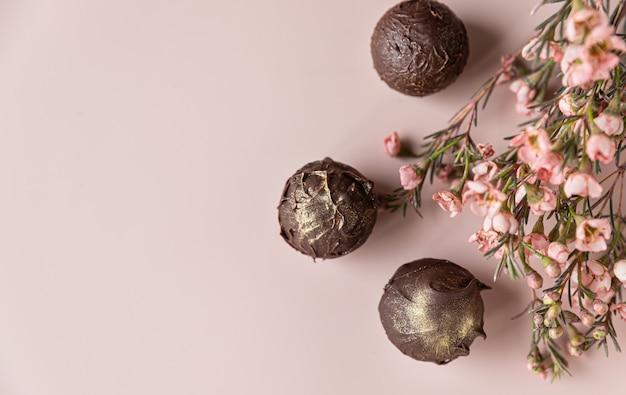 분홍색 꽃으로 장식 된 분홍색 표면에 초콜릿 트뤼플