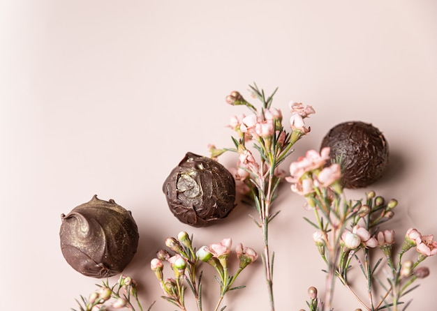 Chocolate truffles on a pink surface decorated with pink flowers
