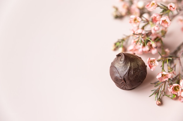 Chocolate truffles on a pink surface with pink flowers