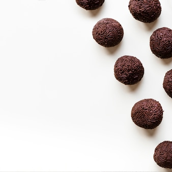 Chocolate truffles in a row on white background