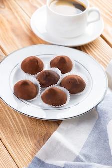 木製のテーブルのプレートにチョコレートトリュフのお菓子をクローズアップ
