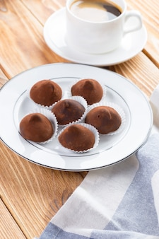 Chocolate truffles sweets in plate on wooden table close up