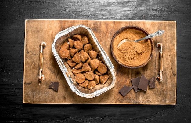 Chocolate truffles with cocoa powder on the board  on the black chalkboard