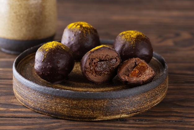 갈색 나무 테이블에 오렌지 필링을 넣은 초콜릿 트러플