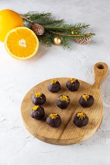 크리스마스 공이 있는 가문비나무 가지의 배경에 오렌지를 넣은 초콜릿 트러플