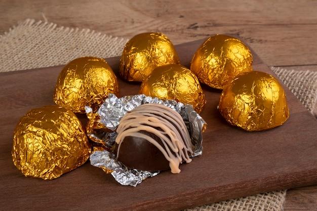 나무 커팅 보드에 적층 종이로 싸인 초콜릿 트뤼플
