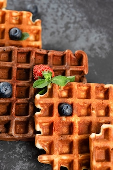 Chocolate and vanilla belgian waffles with fresh berries on a ceramic plate