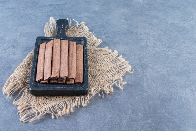 Chocolate wafer rolls in a board on a texture , on the marble background.