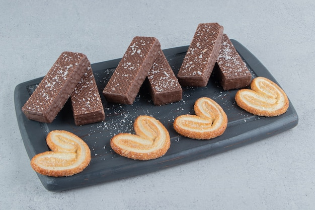 초콜릿 웨이퍼와 대리석 바탕에 블랙 보드에 색다른 쿠키.