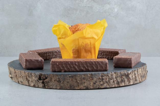 Шоколадные вафли вокруг кекса на доске на мраморном фоне.