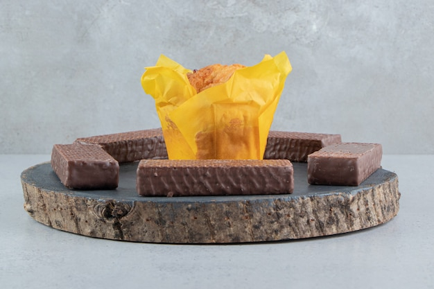 Wafer al cioccolato intorno a un cupcake su una tavola su sfondo di marmo.