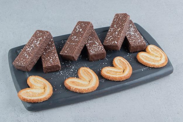 Wafer al cioccolato e biscotti a fiocchi su un bordo nero su sfondo marmo.
