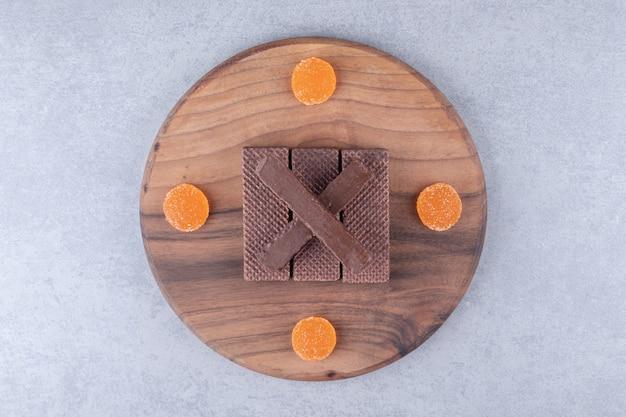 Wafer al cioccolato e marmellate su tavola di legno su marmo