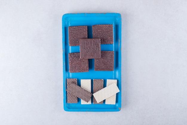 Wafer al cioccolato su un piatto di legno su un tavolo di marmo.