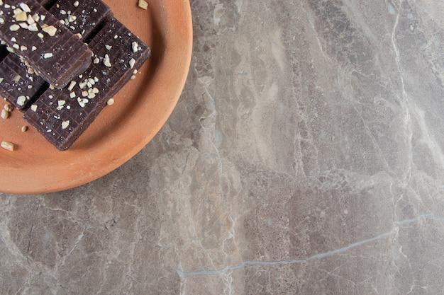 Waffle al cioccolato su un piatto di argilla su marmo.