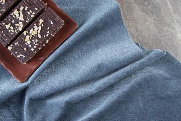 Шоколадные вафли на блюде на кусочках ткани по мрамору.