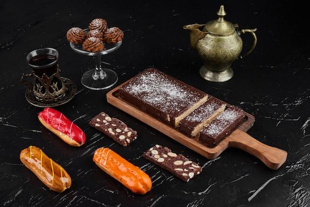 クッキーとエクレアが付いている木製の大皿にチョコレートワッフル。