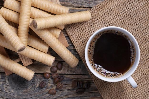 素朴なテーブル、上面図にチョコレートワッフルロールとコーヒーのカップ